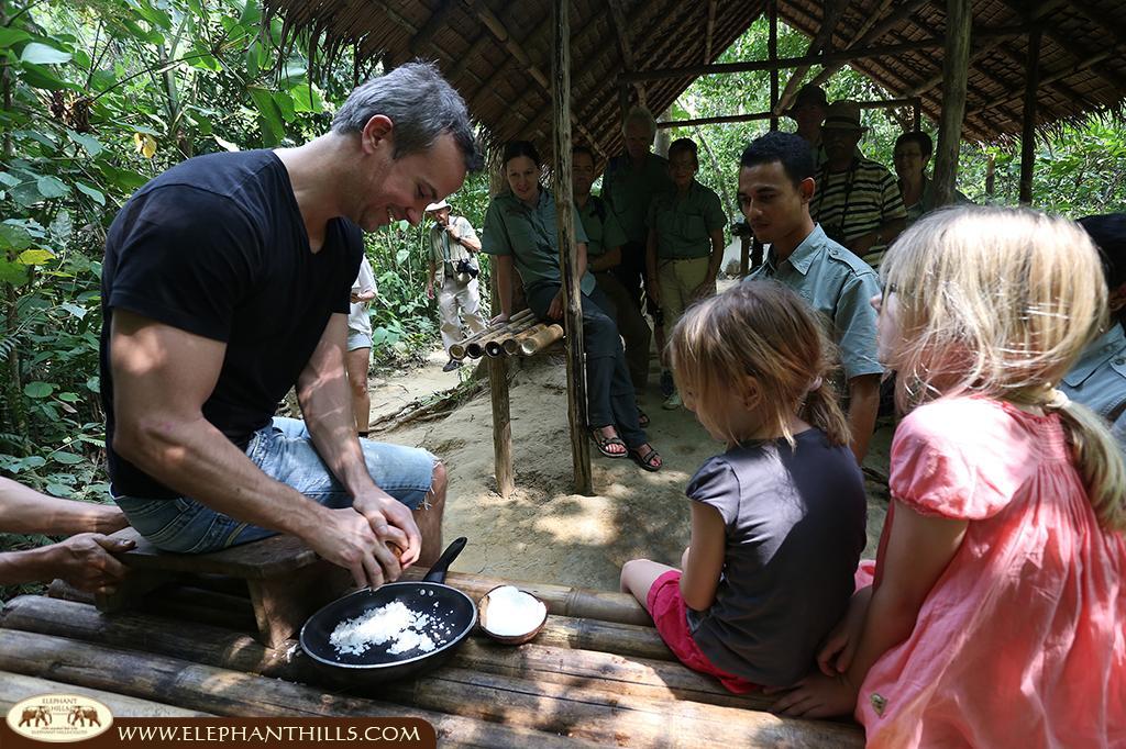 Grating fresh coconuts to prepare a fresh coconut milk for Tom Kha Gai in the Elephant Hills jungle kitchen