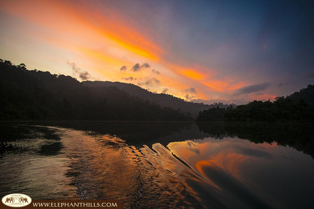 The beautiful red orange sky during sunset is reflected in the waters of Cheow Larn Lake